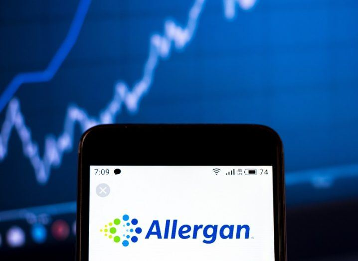 Top of a smartphone screen with the Allergan logo on it against a backdrop of a shares ticker screen.