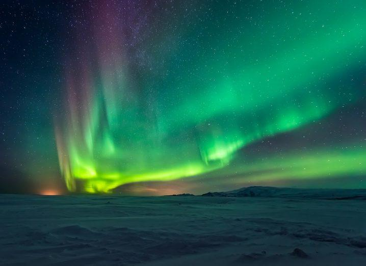 Green and purple northern lights seen over a large, snowy landscape.
