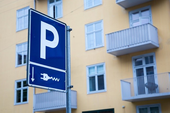 A blue parking sign with a charging point indicator beneath with an apartment block in the background.