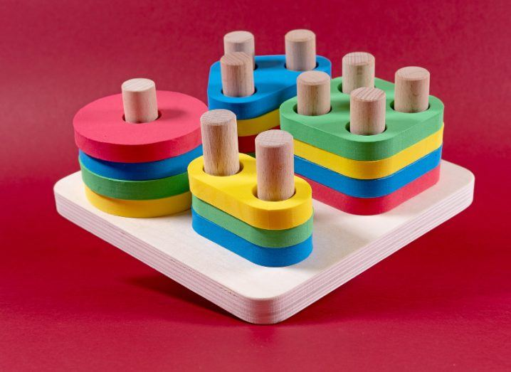 Colourful geometric shapes sorted in stacks on a wooden peg board, floating on a raspberry-red background.