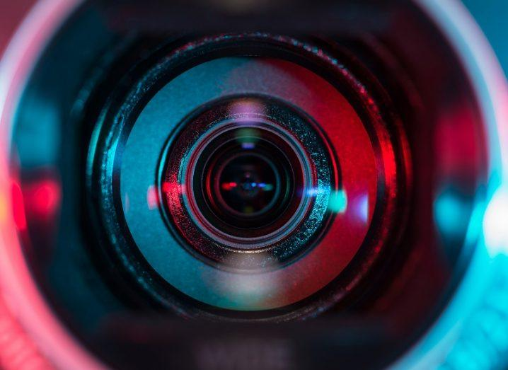 Close-up of a camera lens shrouded in red and blue light.
