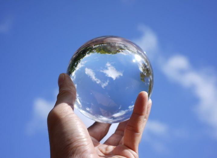 A hand holds up a crystal ball to the sky and in it you can see a cloud.