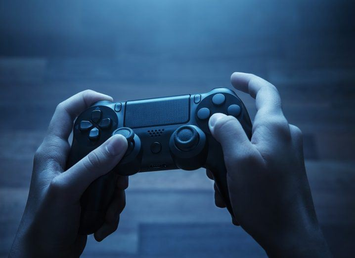 Pair of hands holding a PS4 controller in a dark room lit up by a TV screen out of shot.