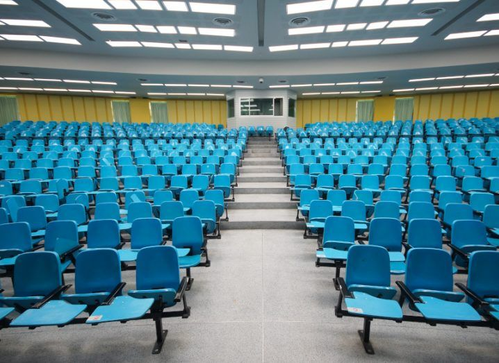 A lecturer's view of an empty classroom, with tiered blue seats for students stretching into the background.