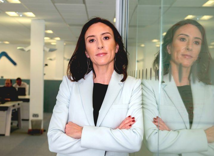 A confident woman in a white blazer leans against a glass wall in an office with her arms folded, her reflection clearly visible.