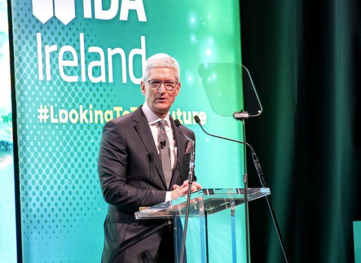 Tim Cook on stage at a podium in the National Concert Hall with a screen behind him bearing the IDA Ireland logo.