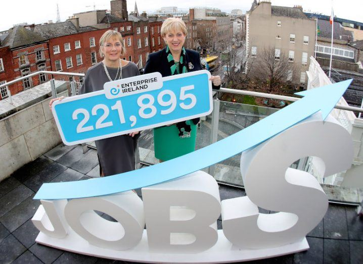 Julie Sinnamon and Heather Humphreys stand on a roof, holding a sign with the figure 221,895 on it, behind another sign that reads 'Jobs'.