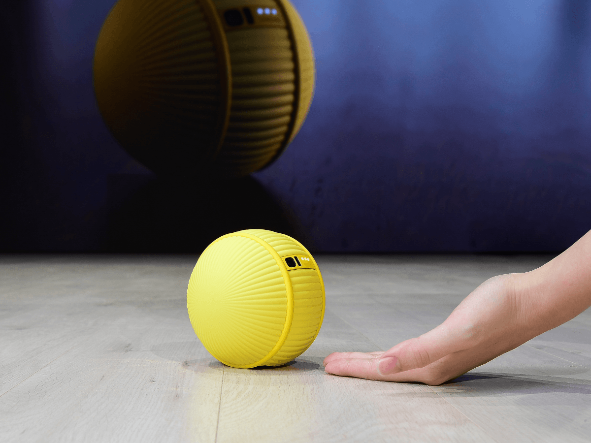 A yellow, tennis ball-sized robot rolls on the floor beside a human's hand. It has a small black camera on it.