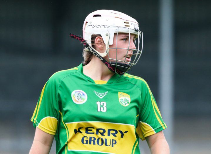 A Kerry camogie player in a green and gold jersey and protective helmet glances across the playing field.