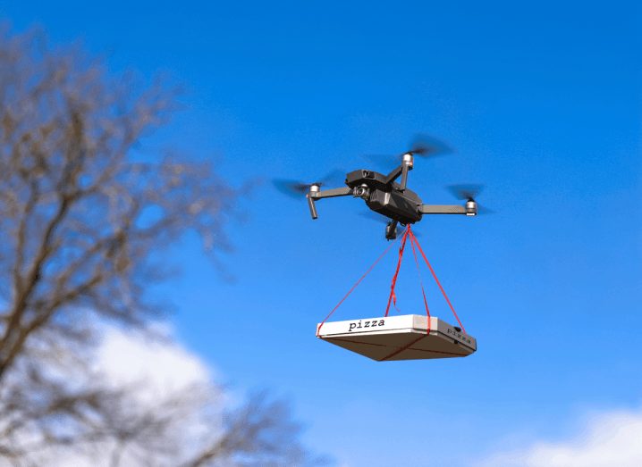 A pizza tied to a black drone that is flying in a blue sky.