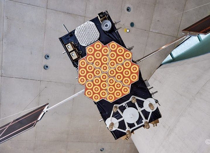 Model of a Galileo satellite hanging from a concrete ceiling.