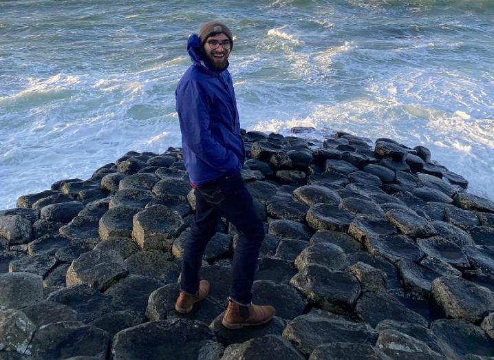 Augusts Pendleton in a blue jacket and grey hat standing on the Giant's Causeway.