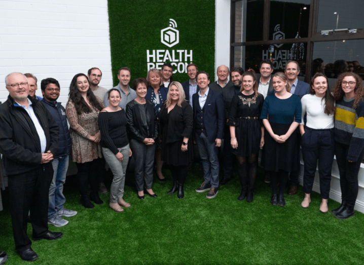A large group of people stand on an astro-turf floor, in front of a sign that reads 'Health Beacon'.