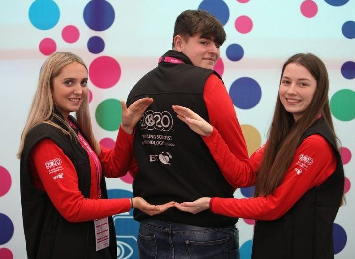 Three BT Young Scientist volunteers, with two pointing to the logo on the middle person's back.