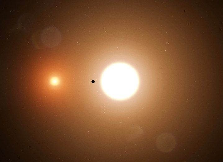 Distant image of a small planet dwarfed by two stars.