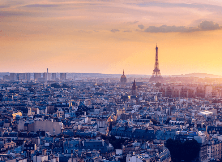The skyline of Paris, the capital of France. The sun is setting and there are clouds high in the sky over the Eiffel Tower.
