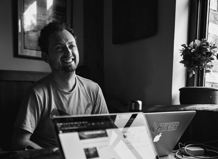 A black and white photograph of a man with short, dark hair and a short goatee sitting at a table using a MacBook Pro with a Hiiker sticker on the back of it.