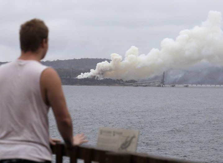 View of a man looking across a body of water at a plume of smoke from the Australian wildfires.