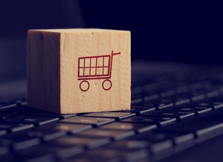 A wooden cube showing a shopping cart icon resting on a computer keyboard.