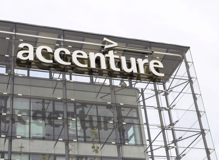 The Accenture logo on the front of a glass building.