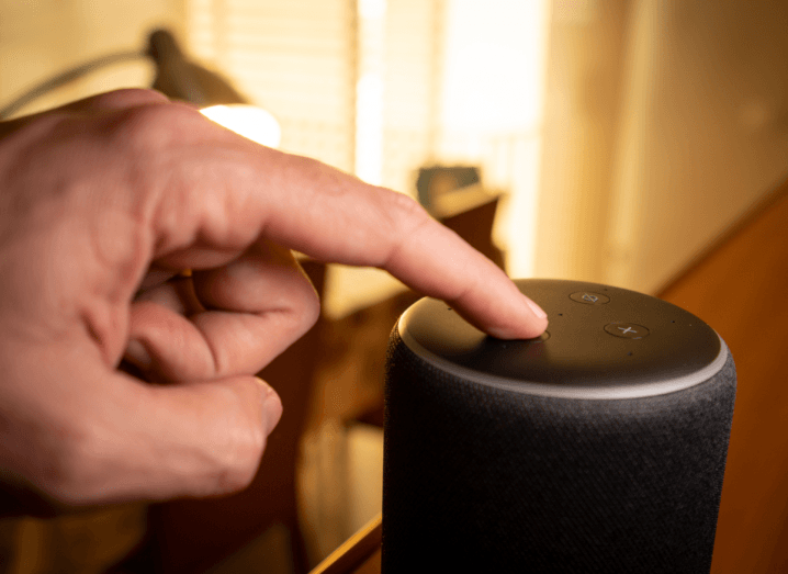 A person touching a button on top of an Amazon Echo device in a living room. The background is out of focus.