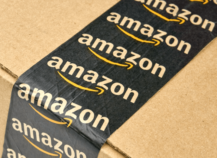 The Amazon logo printed on tape on a shipping box.