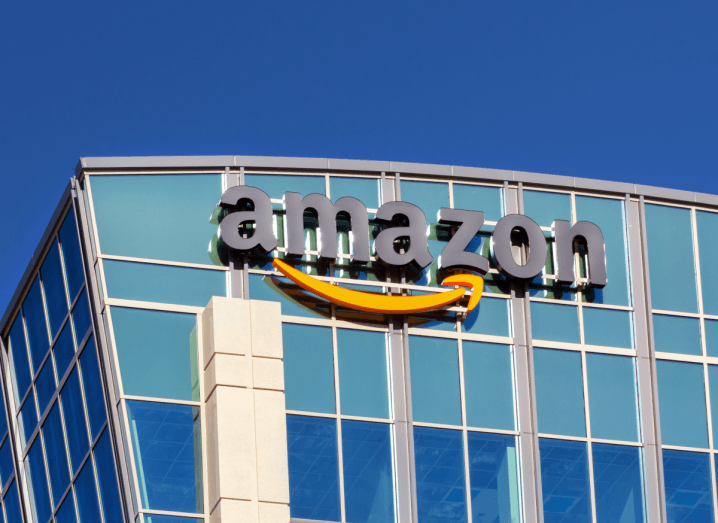 The Amazon logo on the facade of a building under a blue sky.