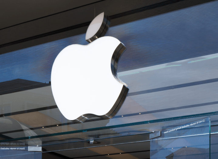 The Apple logo displayed on the front of a glass Apple store.