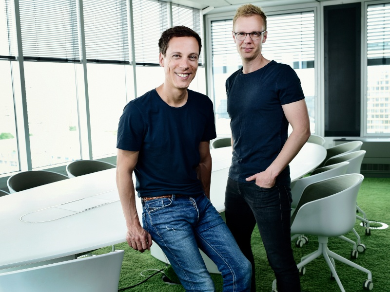 Two men in jeans and dark T-shirts stand in a bright office.