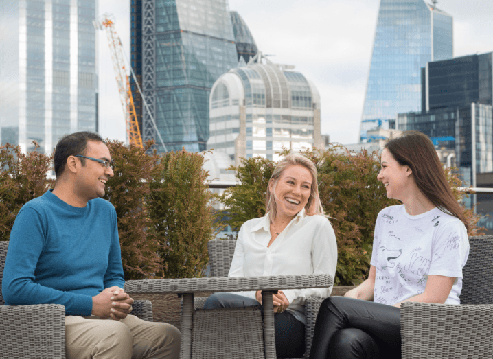 A group of three people sitting at a table chatting in front of the London skyline.
