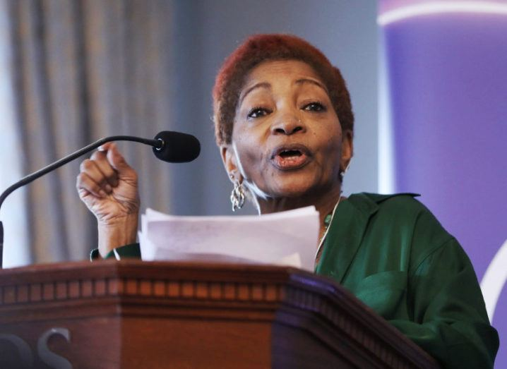 Bonnie Greer stands at a podium, reading a speech from a piece of paper and wearing a green dress.