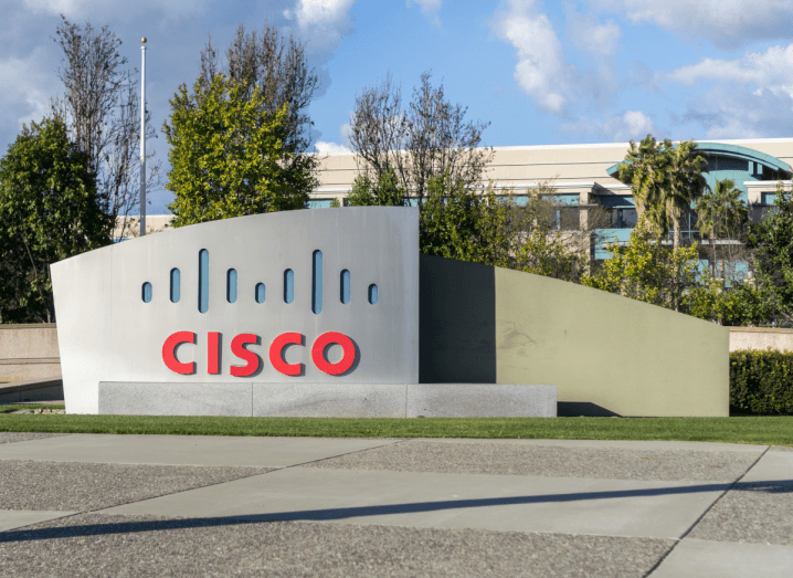 The Cisco logo on a sign in front of a few trees.