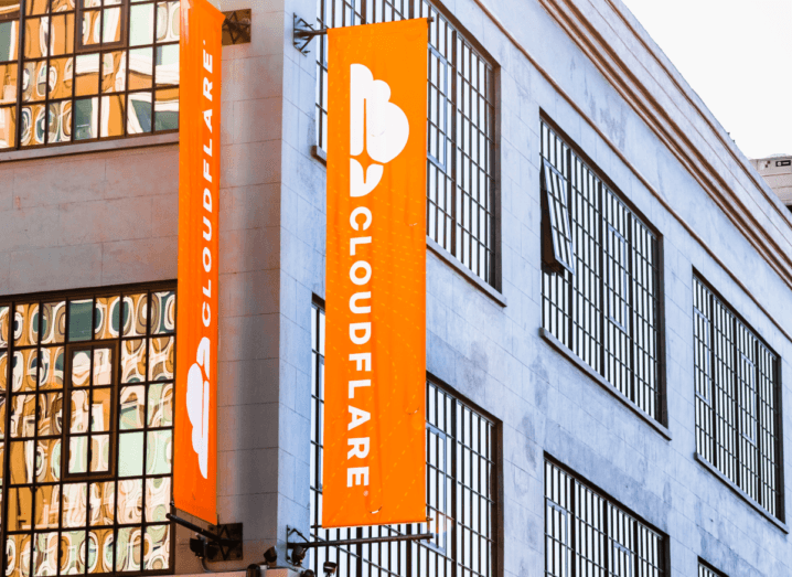 An orange banner outside a grey building with large, square windows. The orange banner has Cloudflare printed on it in white ink.