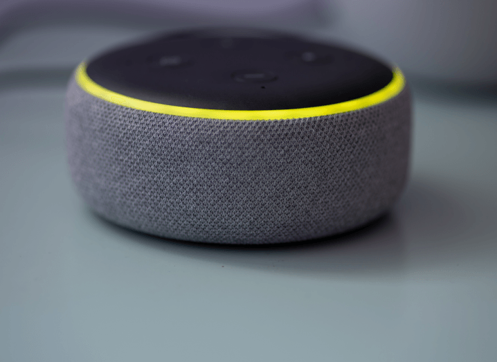 A grey speaker with a black top and a yellow ring lit up around the top of it.