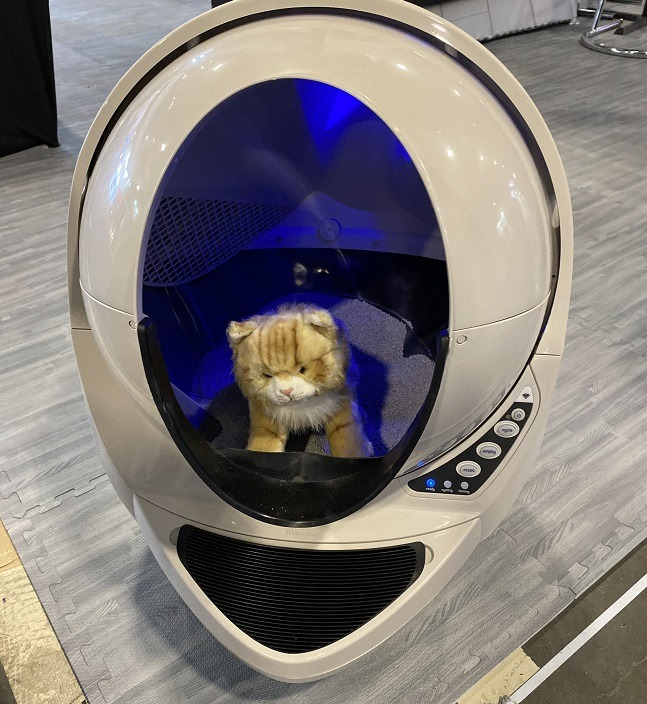 A toy cat sitting in the orb-shaped litter tray device.