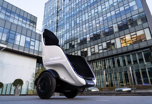 The Segway S-Pod against the backdrop of an office building.