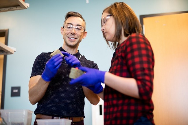 Wil Srubar and a lab student wearing purple gloves and safety goggles while holding the biomaterial in a lab.
