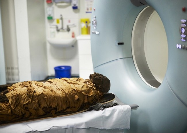 The mummy being put into a CT scanner.