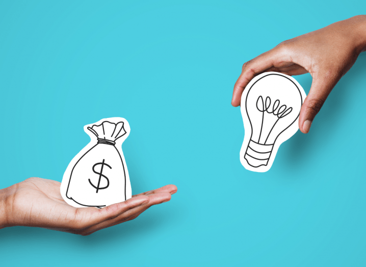 Two hands are edging into frame against a bright blue background. One hand is holding a drawing of a bag with a dollar sign on it, the other hand is holding a drawing of a lightbulb.