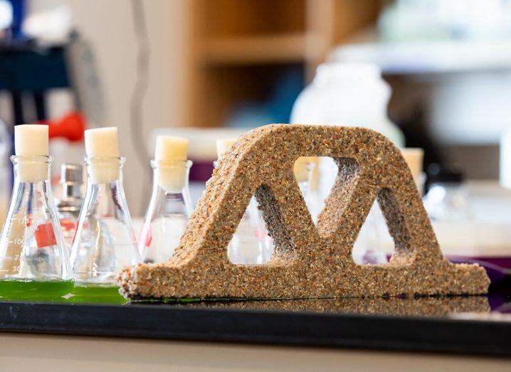 The bio-concrete moulded into a lattice brick shape on a lab table beside beakers filled with green liquid.