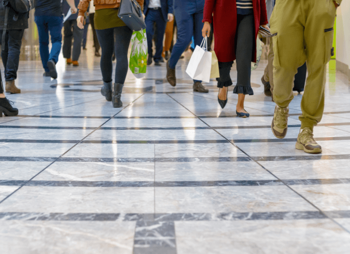 Shoppers walking on a tiled floor.