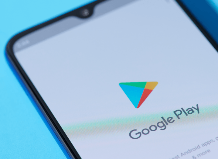 The Google Play store logo displayed on an Android smartphone, which is rested on a blue surface.