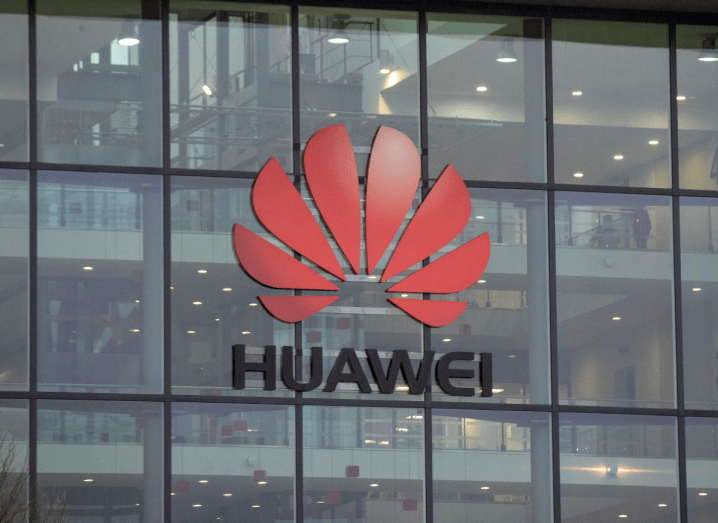 The Huawei logo on the front of a glass building.