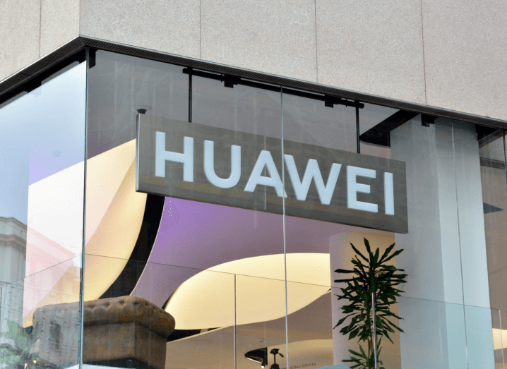 A Huawei sign behind a glass window in a room with a potted plant and grey armchair.