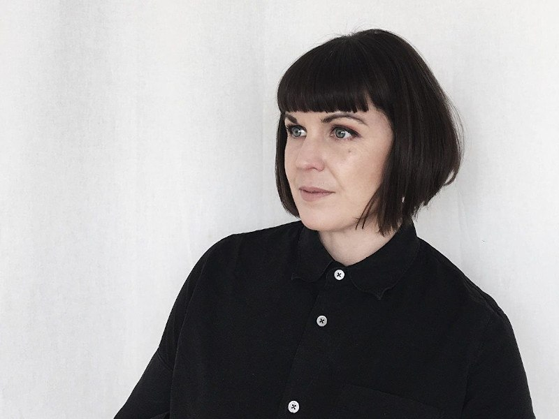 Woman with dark hair and a black shirt sits against a white wall.
