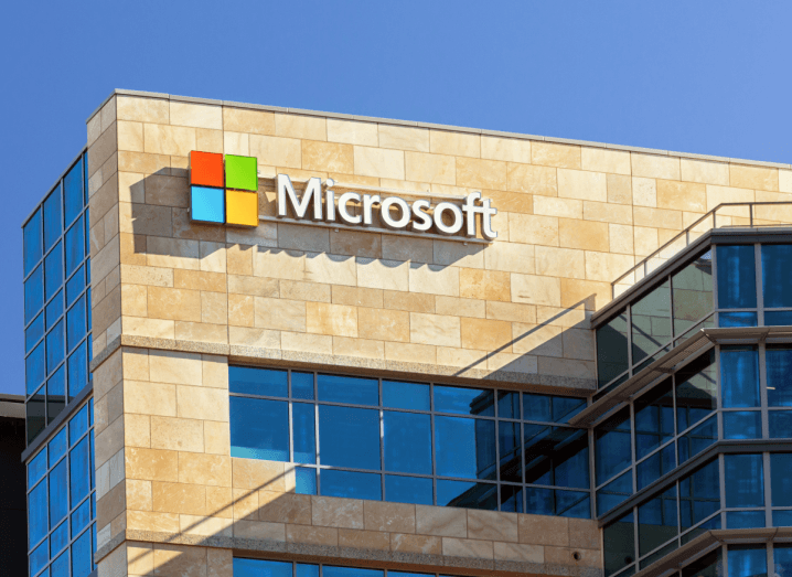 The facade of a Microsoft office with the company's logo displayed above a window. There is a clear blue sky above.
