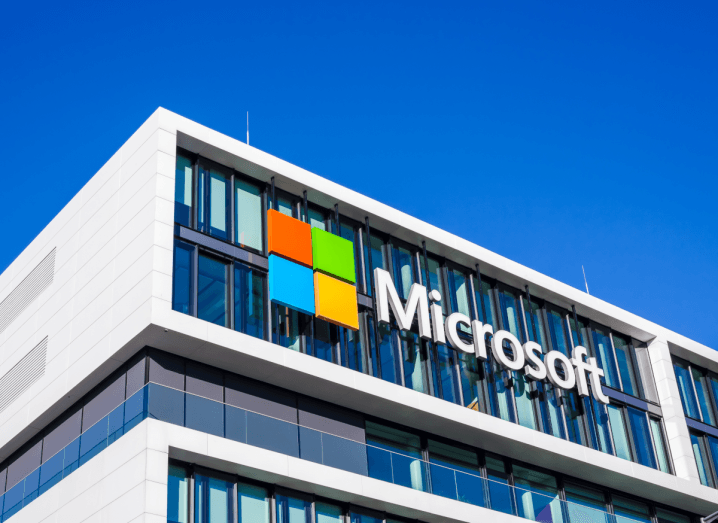 The Microsoft logo on the front of an office building under a sunny sky.