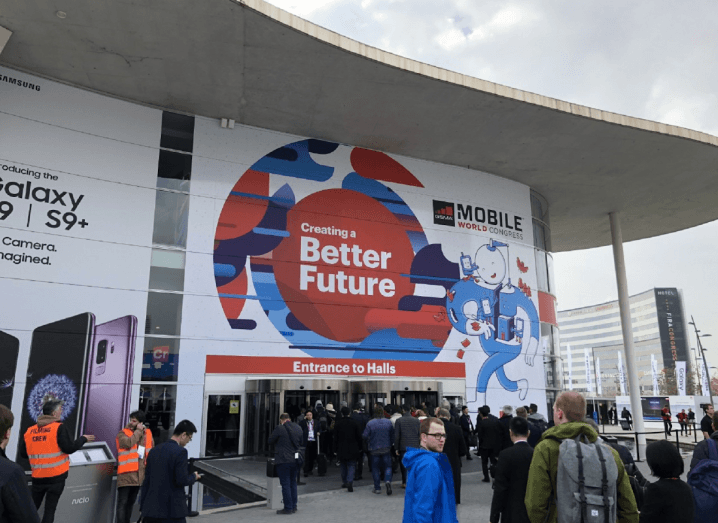 The entrance to MWC in Barcelona. There are lots of people outside queueing to enter the building.