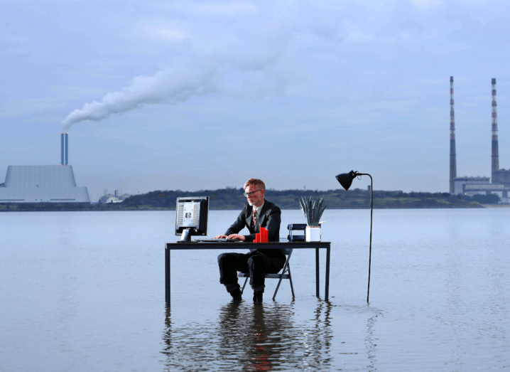 A man sitting at a desk in front of the Poolbeg chimneys and the Ringsend incinerator, working on a computer while his feet are submerged in water, representing rising sea levels.