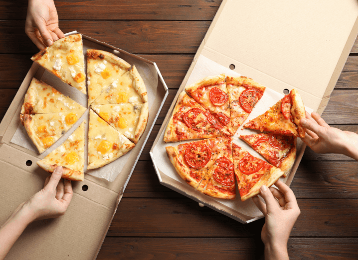 Four hands grabbing different slices of pizza from brown pizza boxes.